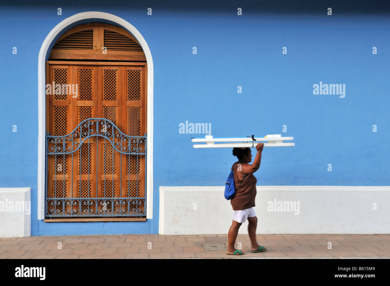 Woman walking past a blue house, Granada, Nicaragua, Central America - Stock Image