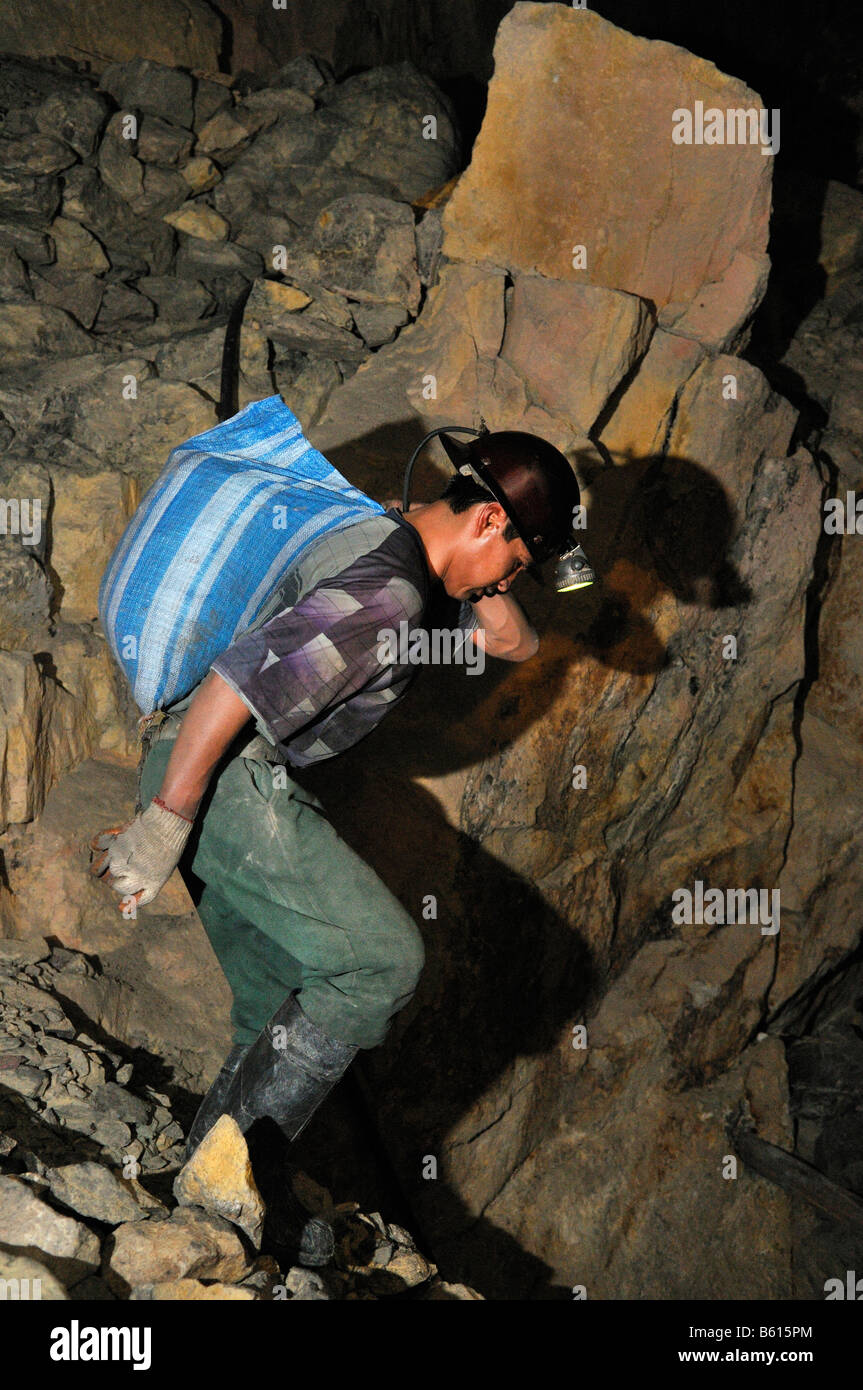 Miner carrying a heavy ore-bearing rock out of the tunnel, Llallagua mining centre, Potosi, Bolivia, South America - Stock Image