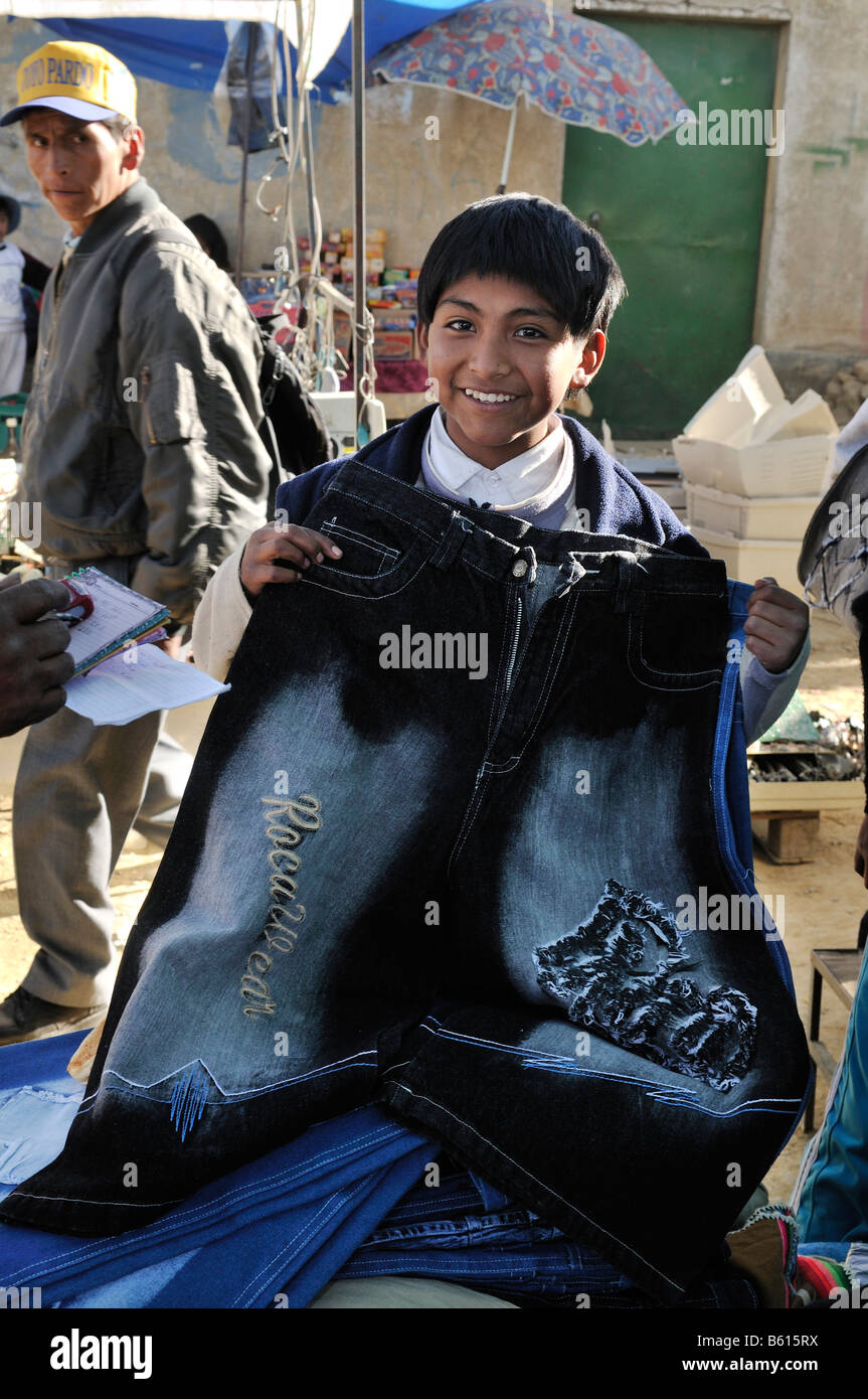 Child labour, 10-year-old boy selling trousers on El Alto market, La Paz, Bolivia, South America - Stock Image