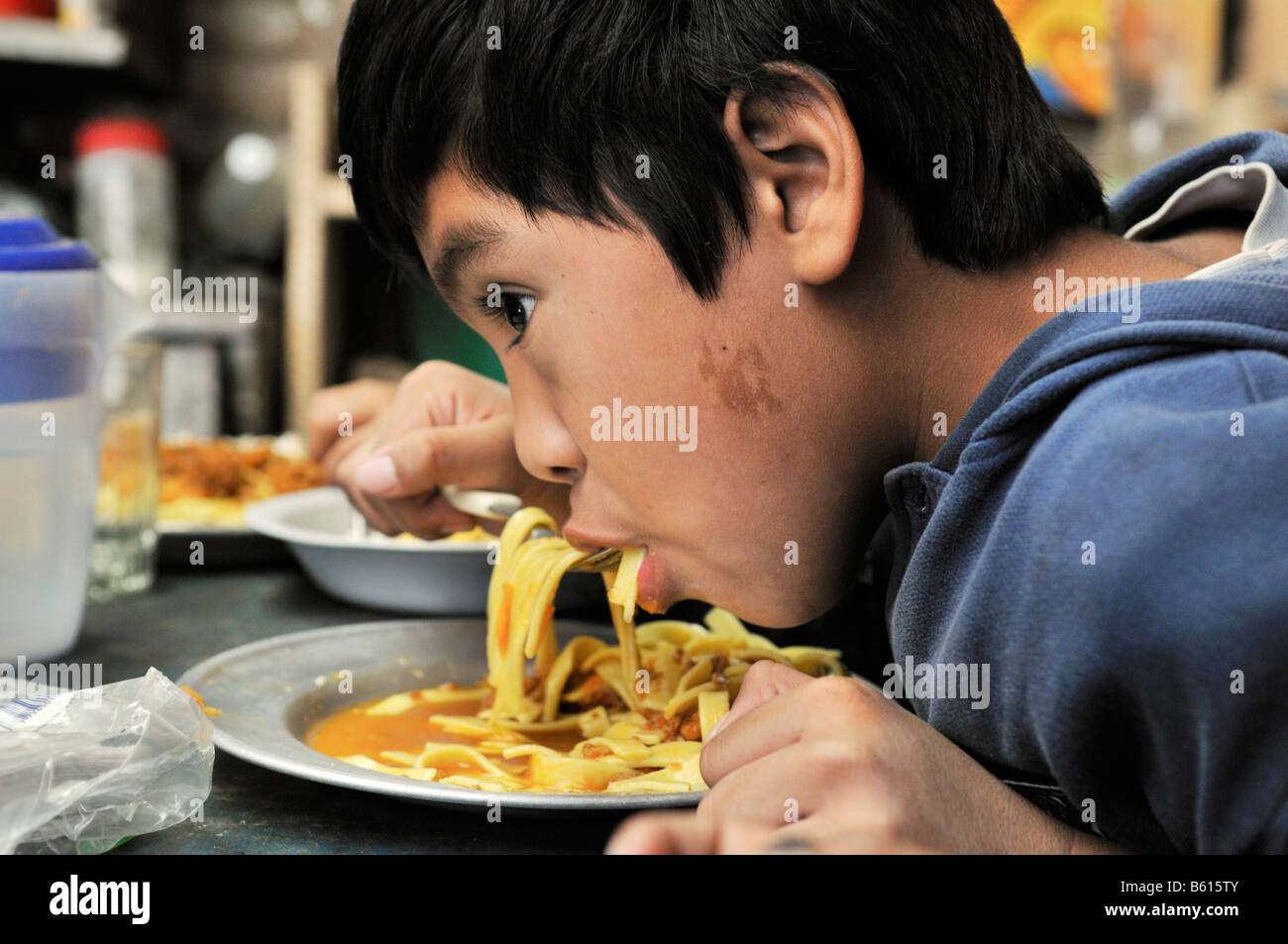 Hungry boy eating noodles, Slum Area Plan 3000, Santa Cruz, Bolivia, South America - Stock Image