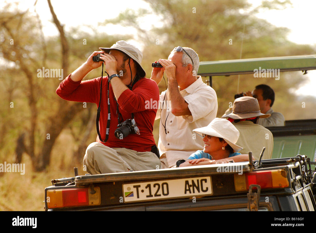 Tourists observing wildlife in Serengeti National Park, Tanzania, Africa - Stock Image