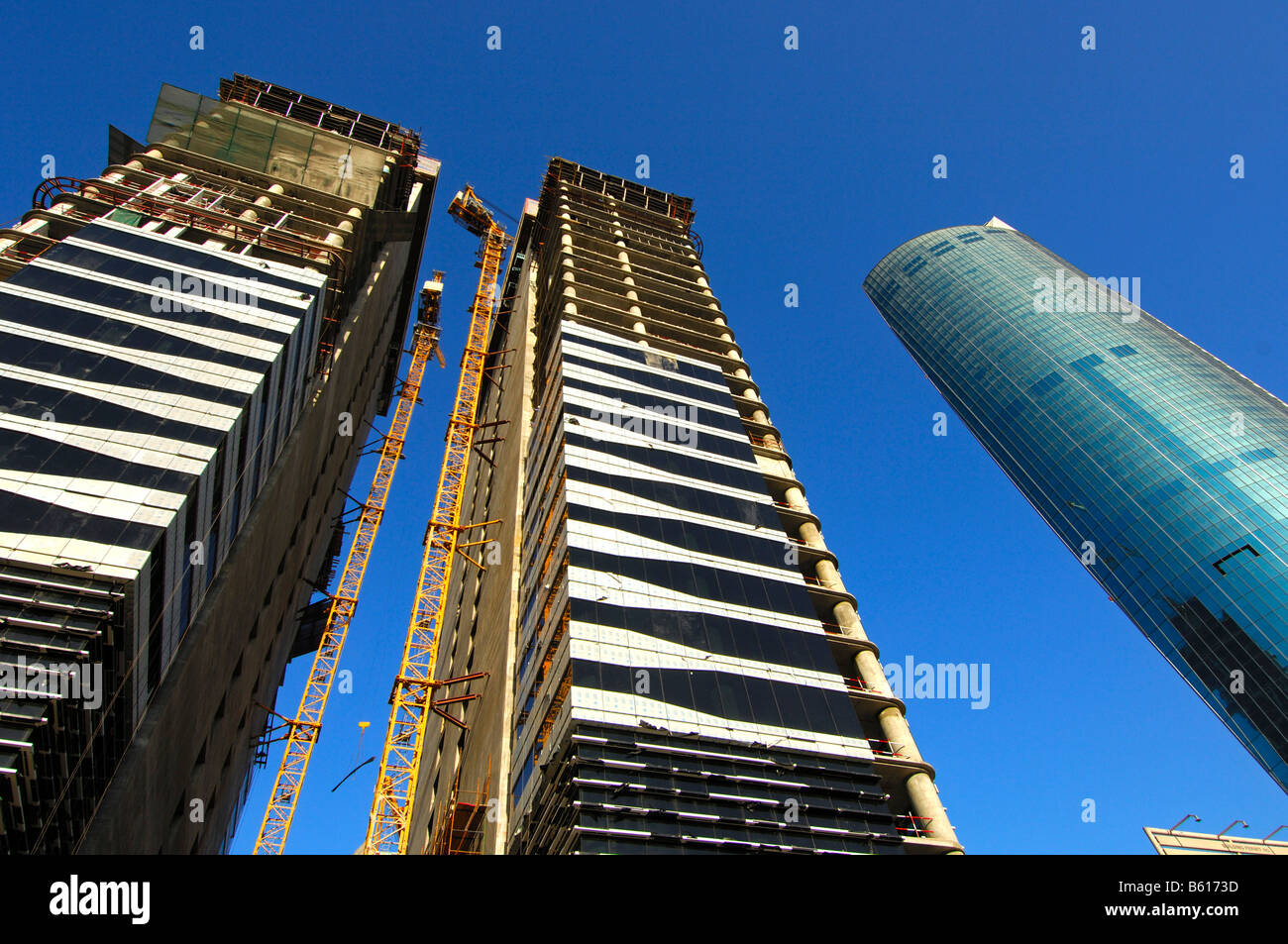Building site on the Sheikh Zayed Road, completed multistory building and the unfinished Twin Towers, Dubai - Stock Image
