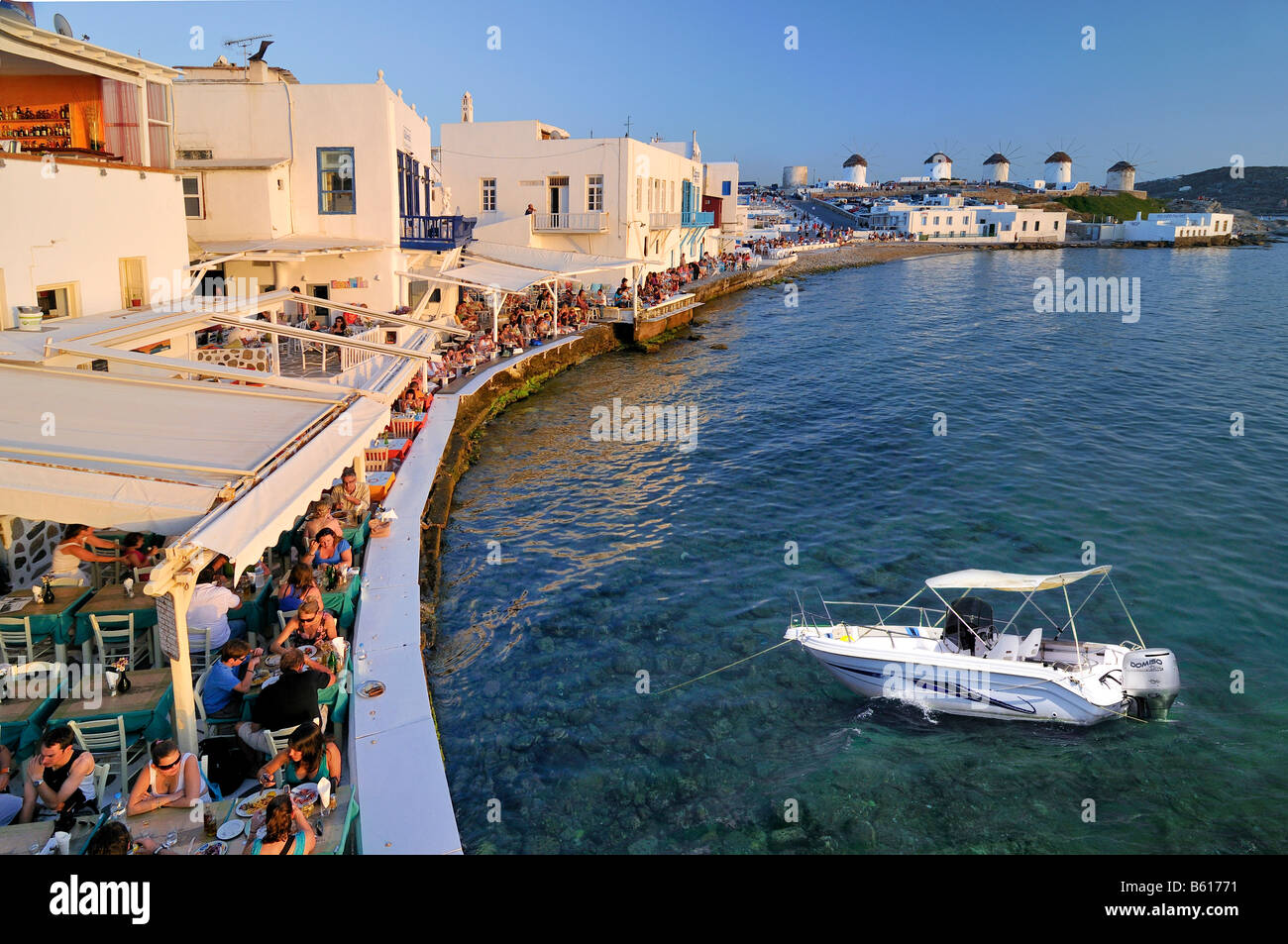 Tourists seated at restaurants in Little Venice and windmills, collage containing a motor yacht, Mykonos Island, - Stock Image