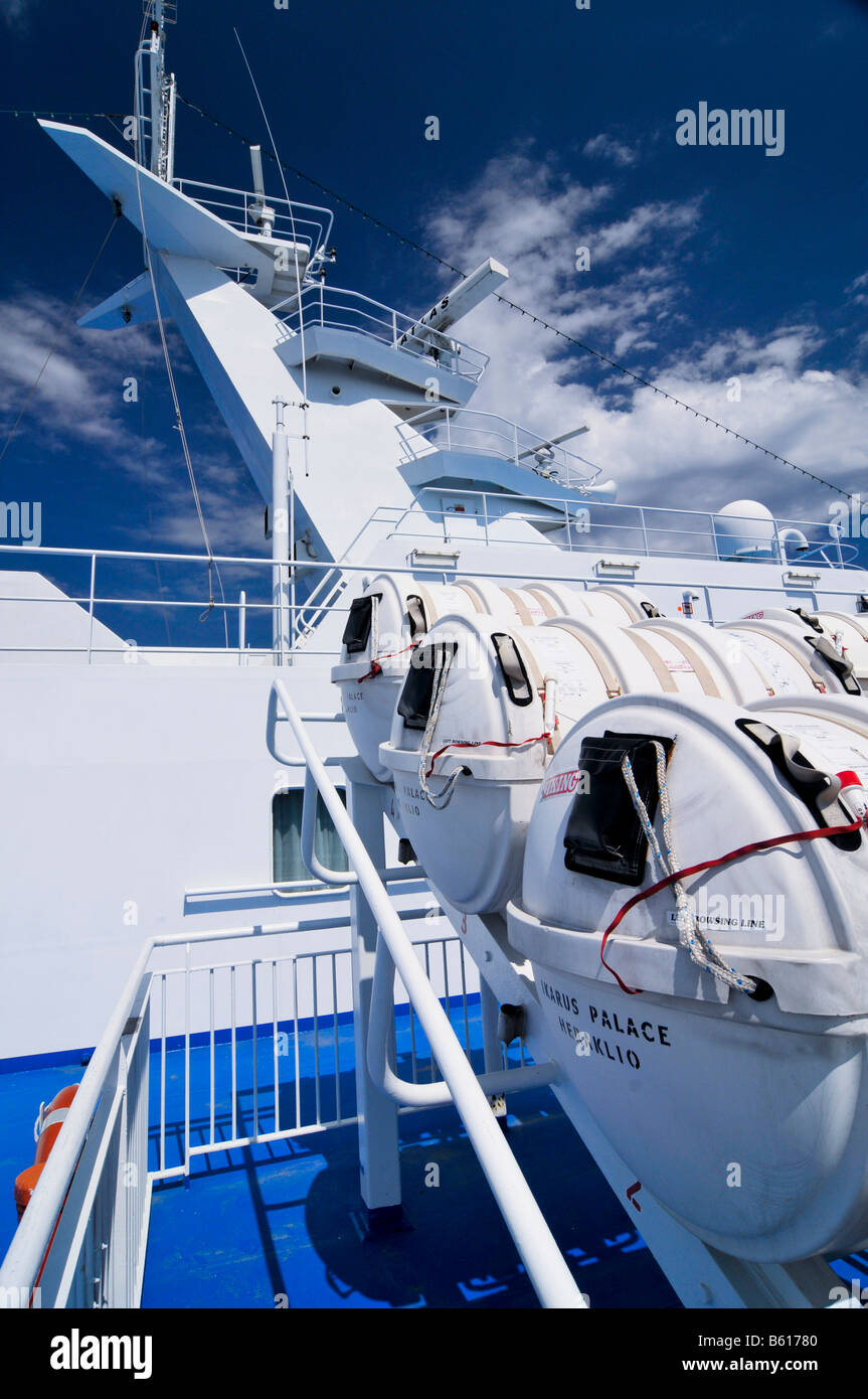 Navigation mast supporting the ship's radar, at front the containers holding inflatable lifeboats on the side - Stock Image