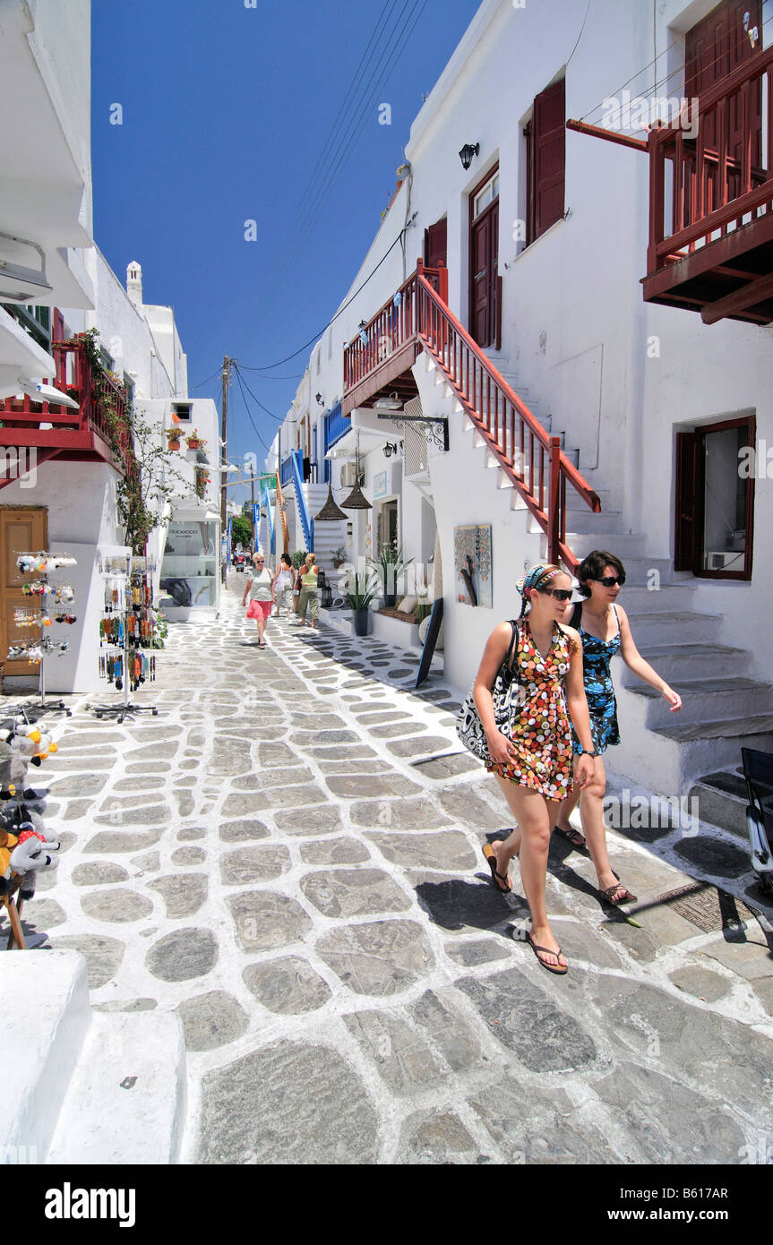 Two Young Women Walking Along A Typical Greek Alley With White