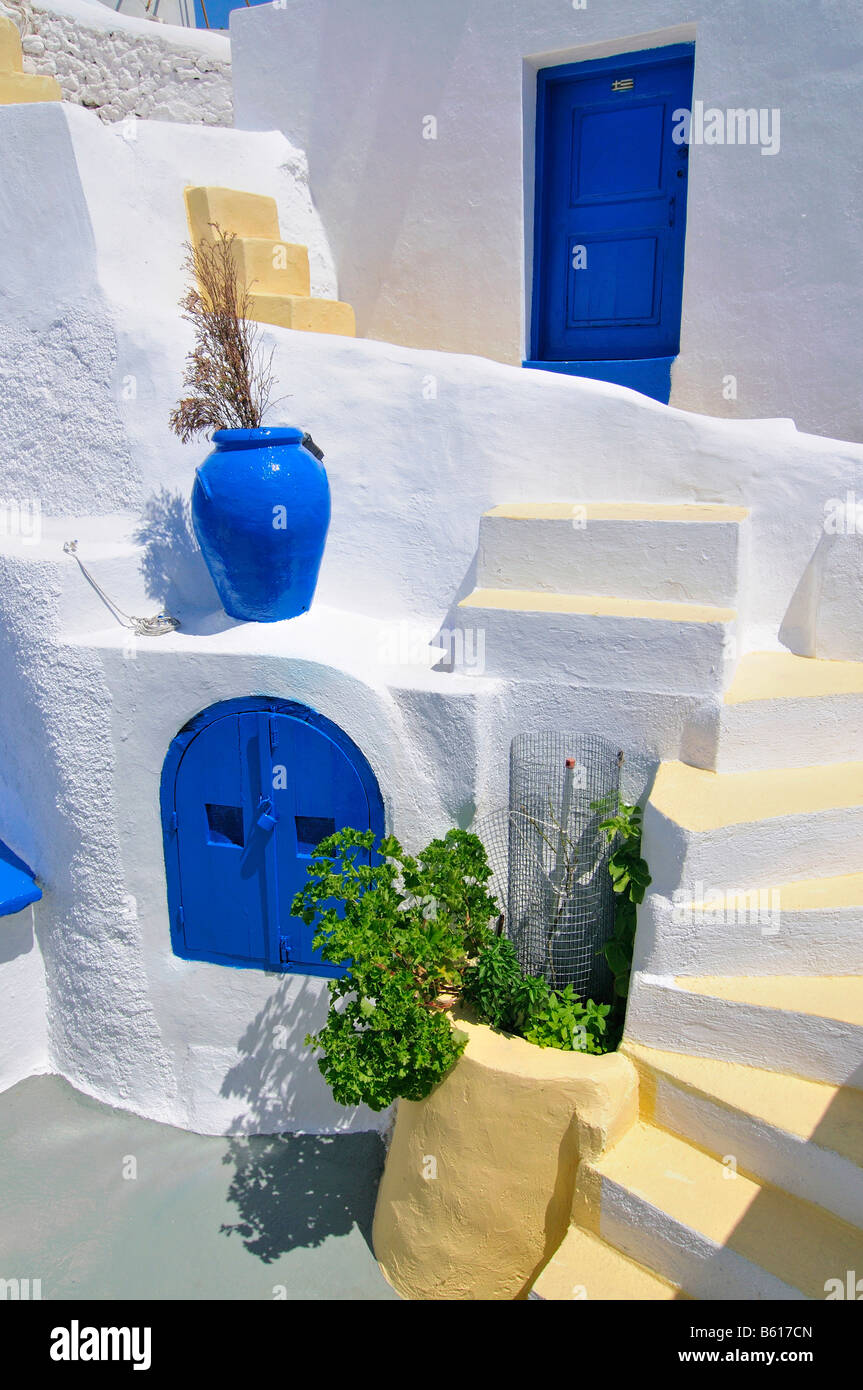 Inner courtyard with blue and yellow elements and a stairway in a typical cycladic architecture style, Oia, Ia, - Stock Image