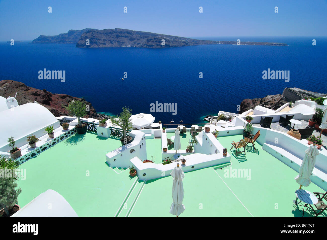 Sun terrace with a green floor and sunshades in front of the blue sea and the volcanic island of Nea Kameni, Oia, - Stock Image