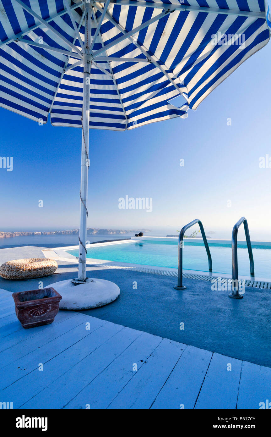 Terrace with a swimming pool and a sunshade in front of the blue sea, Thira, Fira, Santorini, Cyclades, Greece, - Stock Image