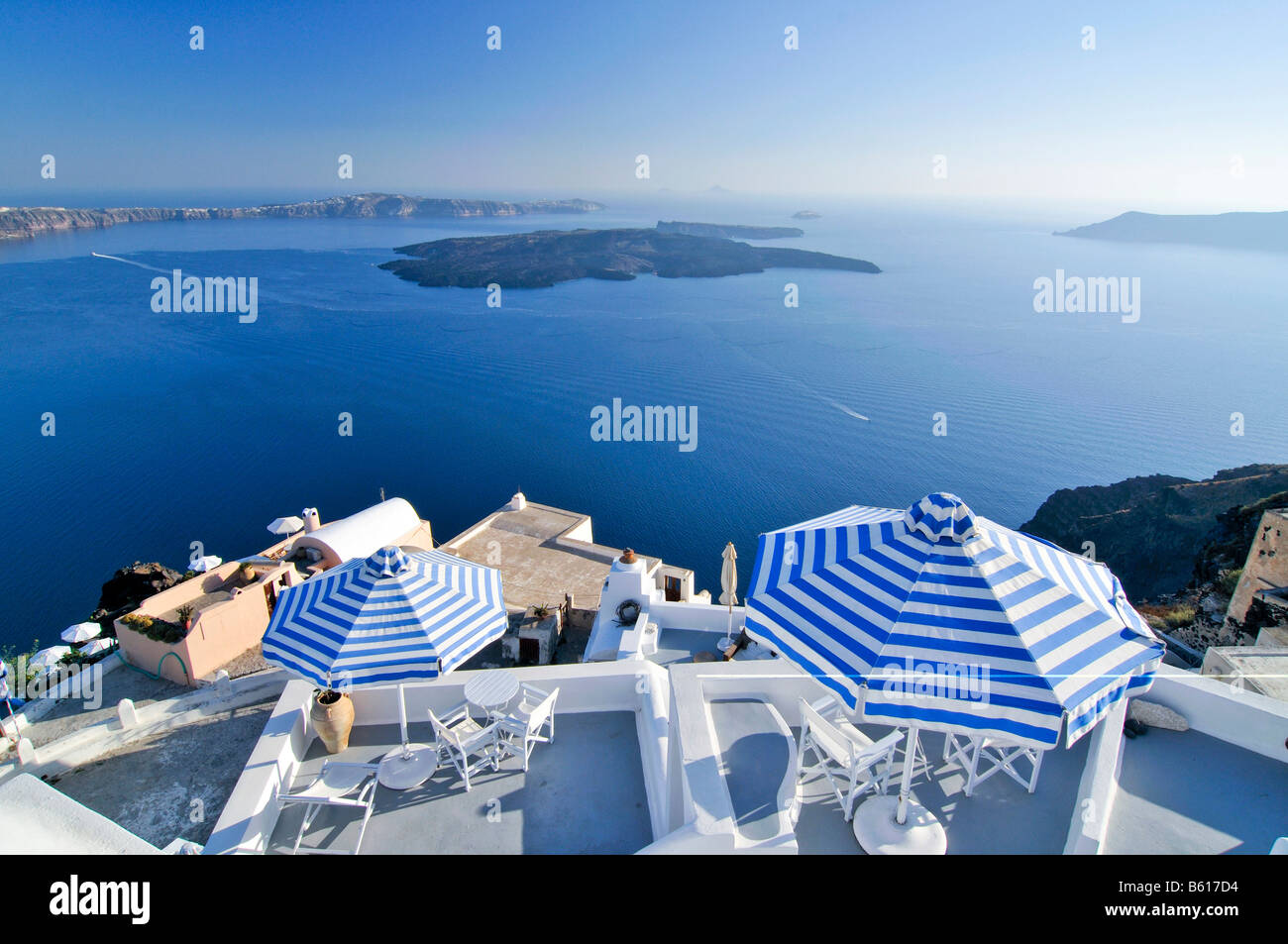 Terraces with blue and white striped sunshades in front of the blue sea and the volcanic island of Nea Kameni, Santorini - Stock Image
