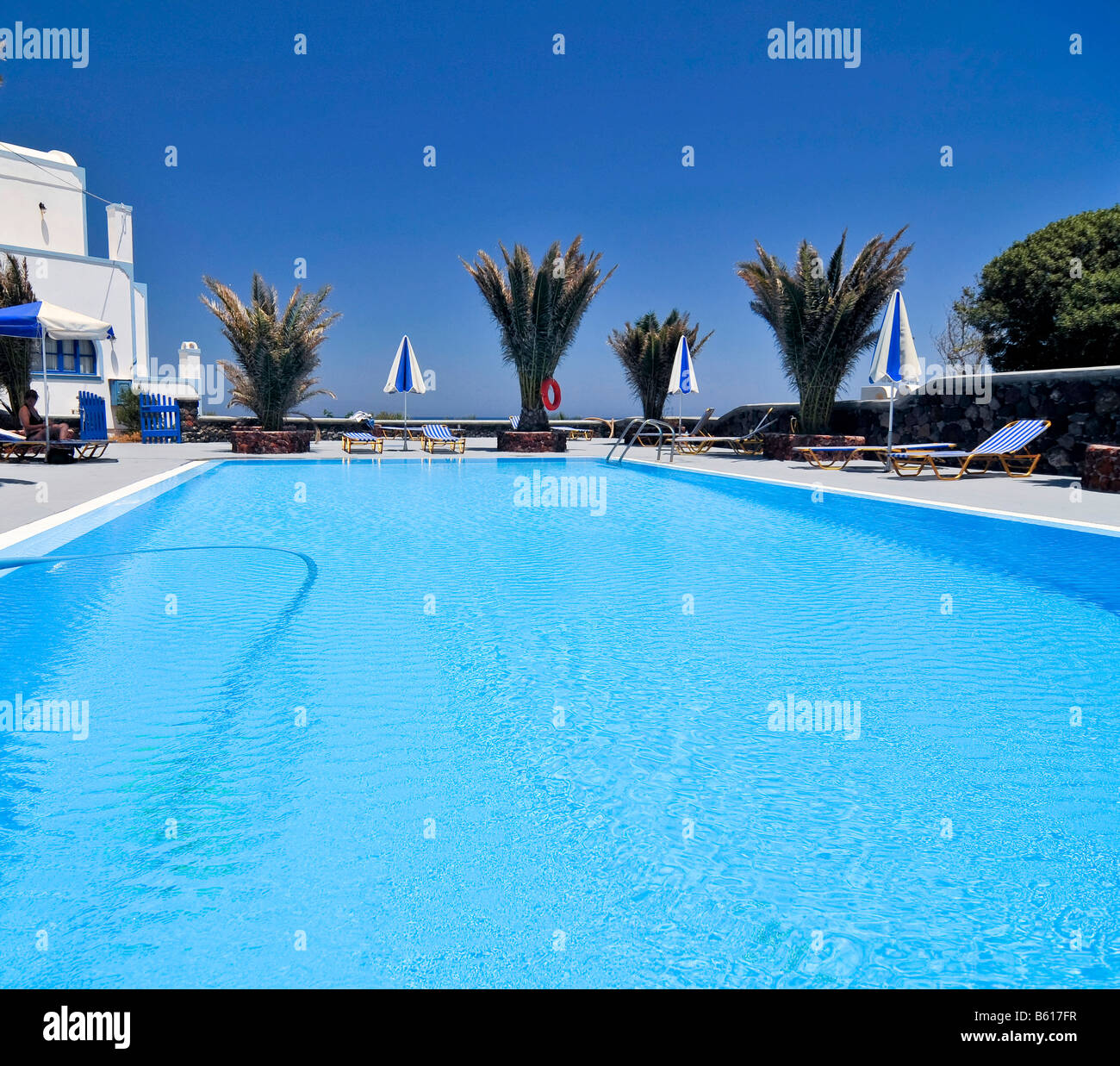 Deserted swimming pool with palms, Santorini, Cyclades, Greece, Europe - Stock Image