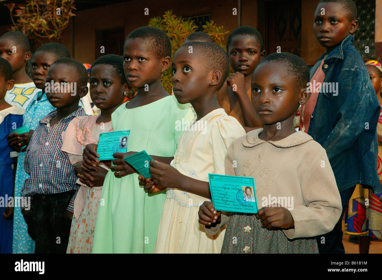 Children displaying their school identification documents for permission to receive school materials, Women's - Stock Image
