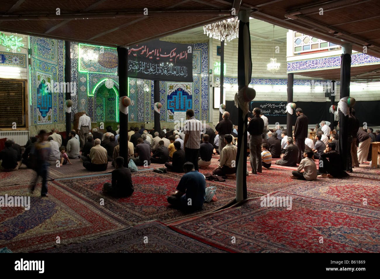 Men praying during Holy Defence Week in Seyedo Shohada mosque in Nazi Anbad Down town Tehran - Stock Image