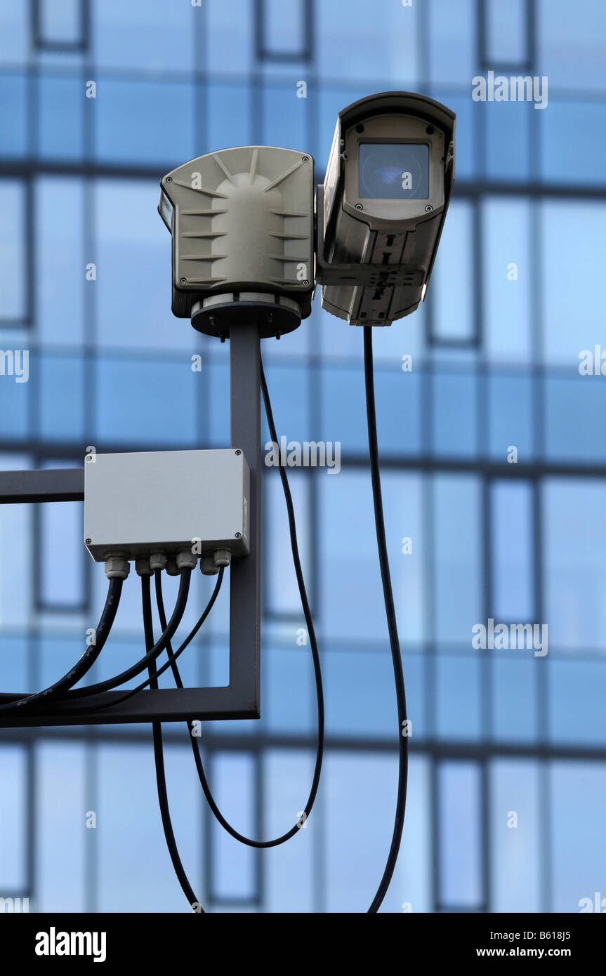 Security, surveillance camera in front of a multistory building - Stock Image