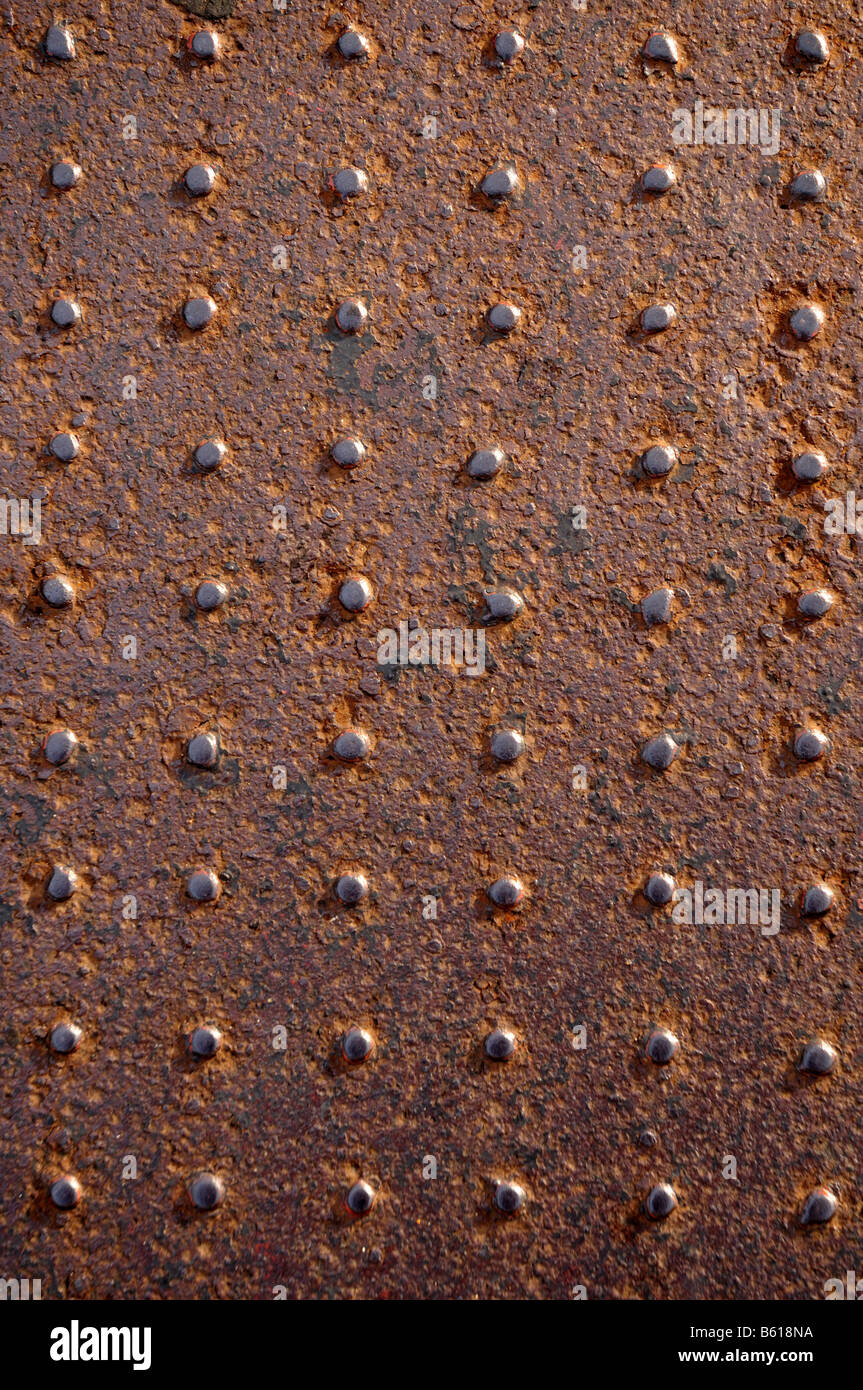 Rusted steel plate covered in rivets - Stock Image