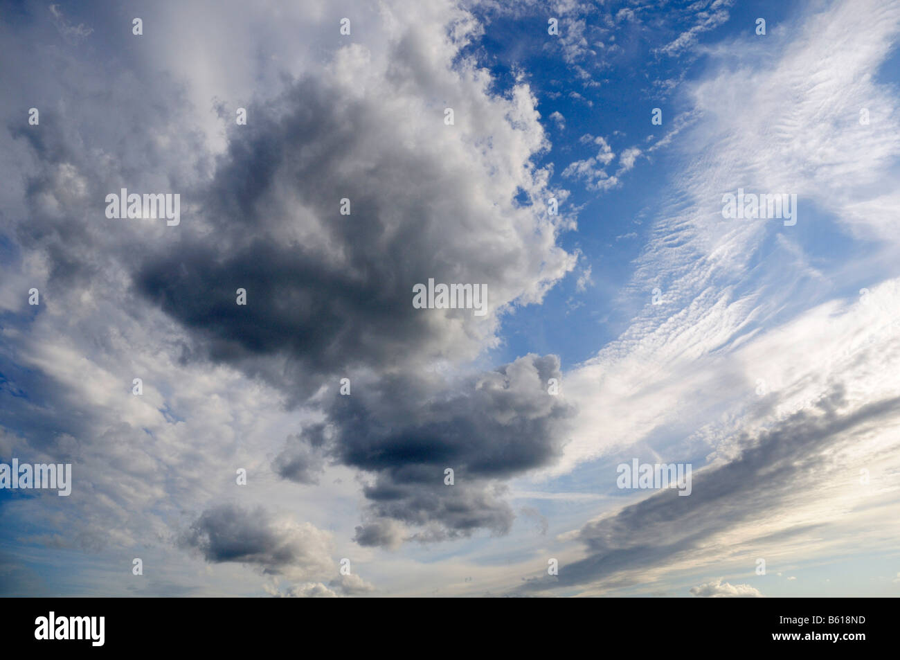 Rain clouds pushing their way in front of sunny weather clouds - Stock Image