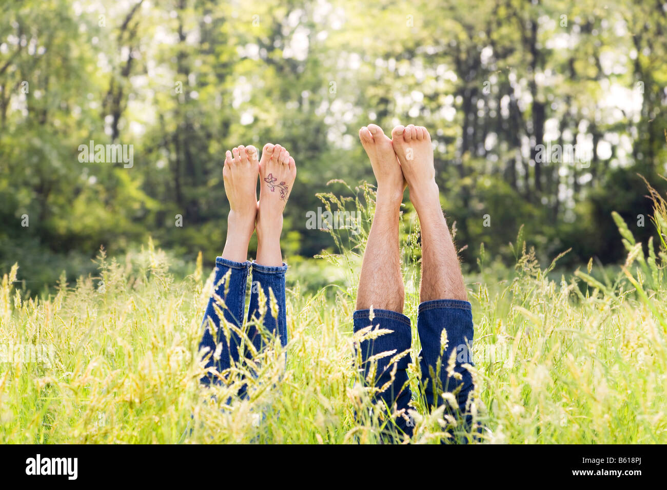 Couple lying in grass stretching their legs up - Stock Image