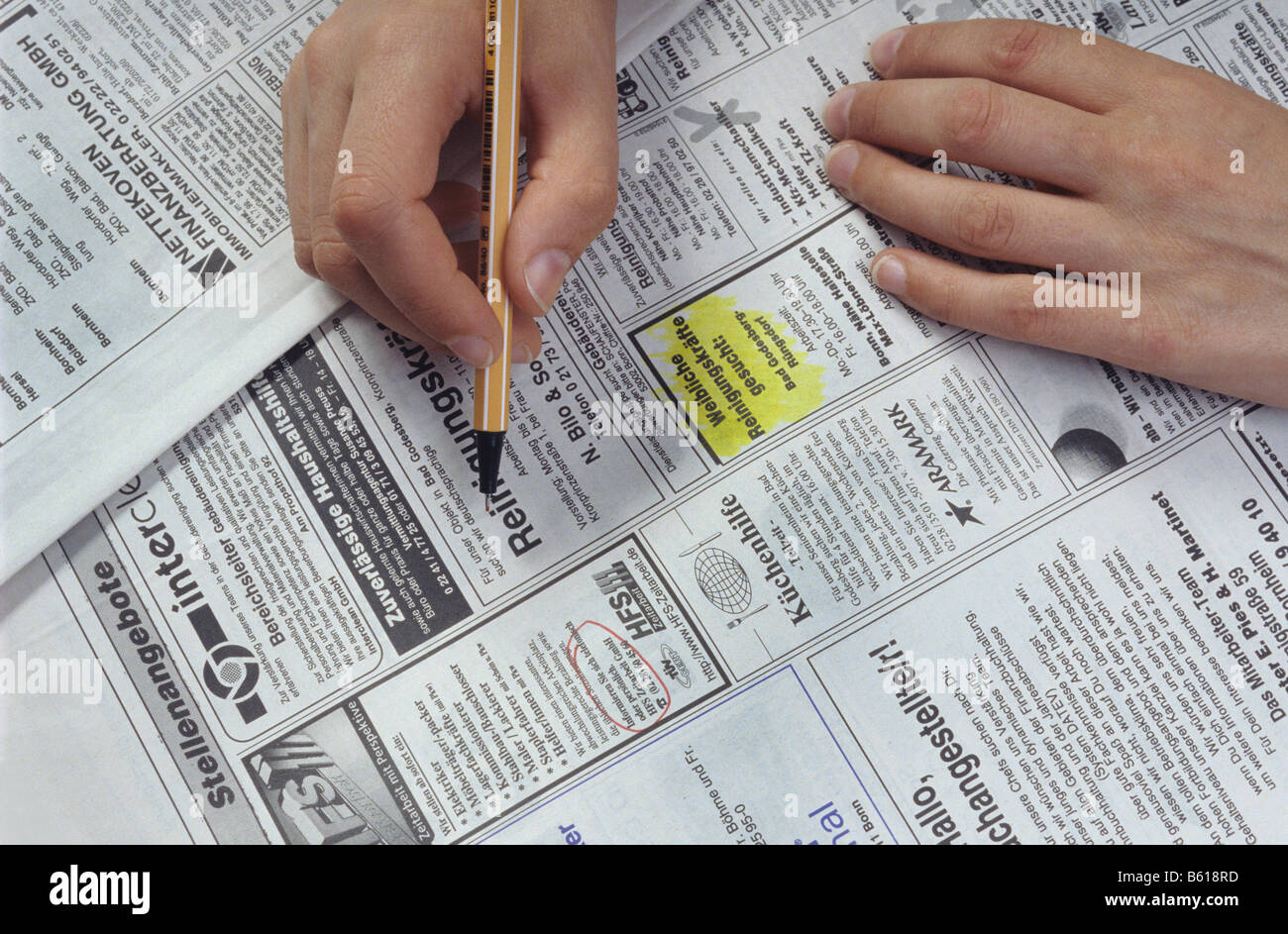 Job search, hand marking job advertisements for cleaning help with a pen, newspaper - Stock Image