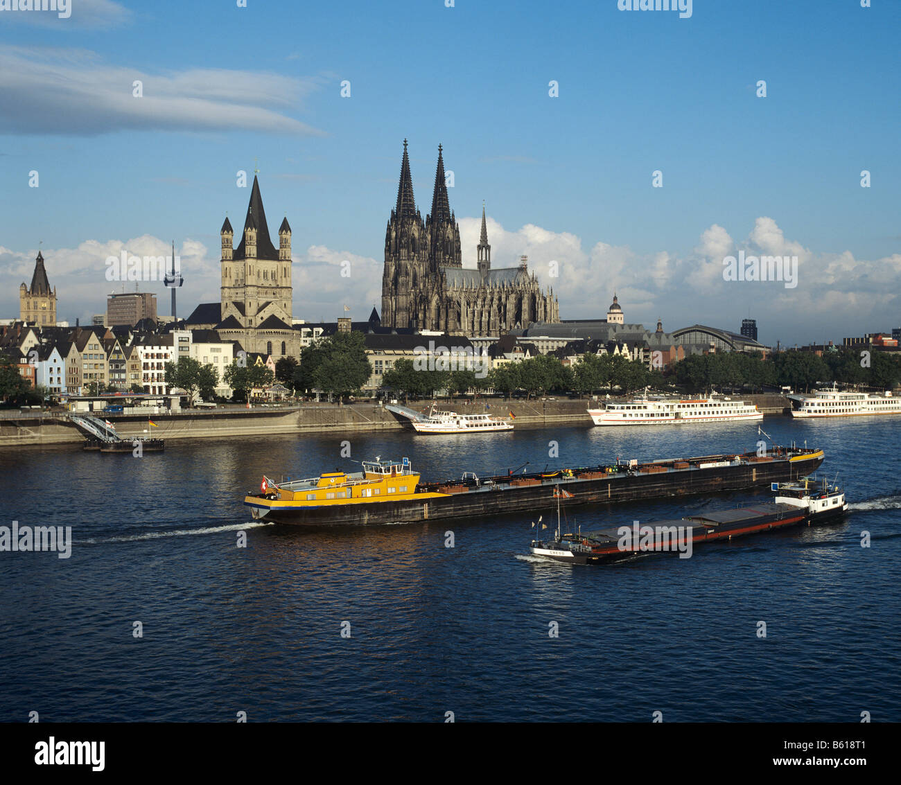 View over the Rhine River to the Cathedral and the Gross St. Martin Church, at front are freight barges and tourists - Stock Image