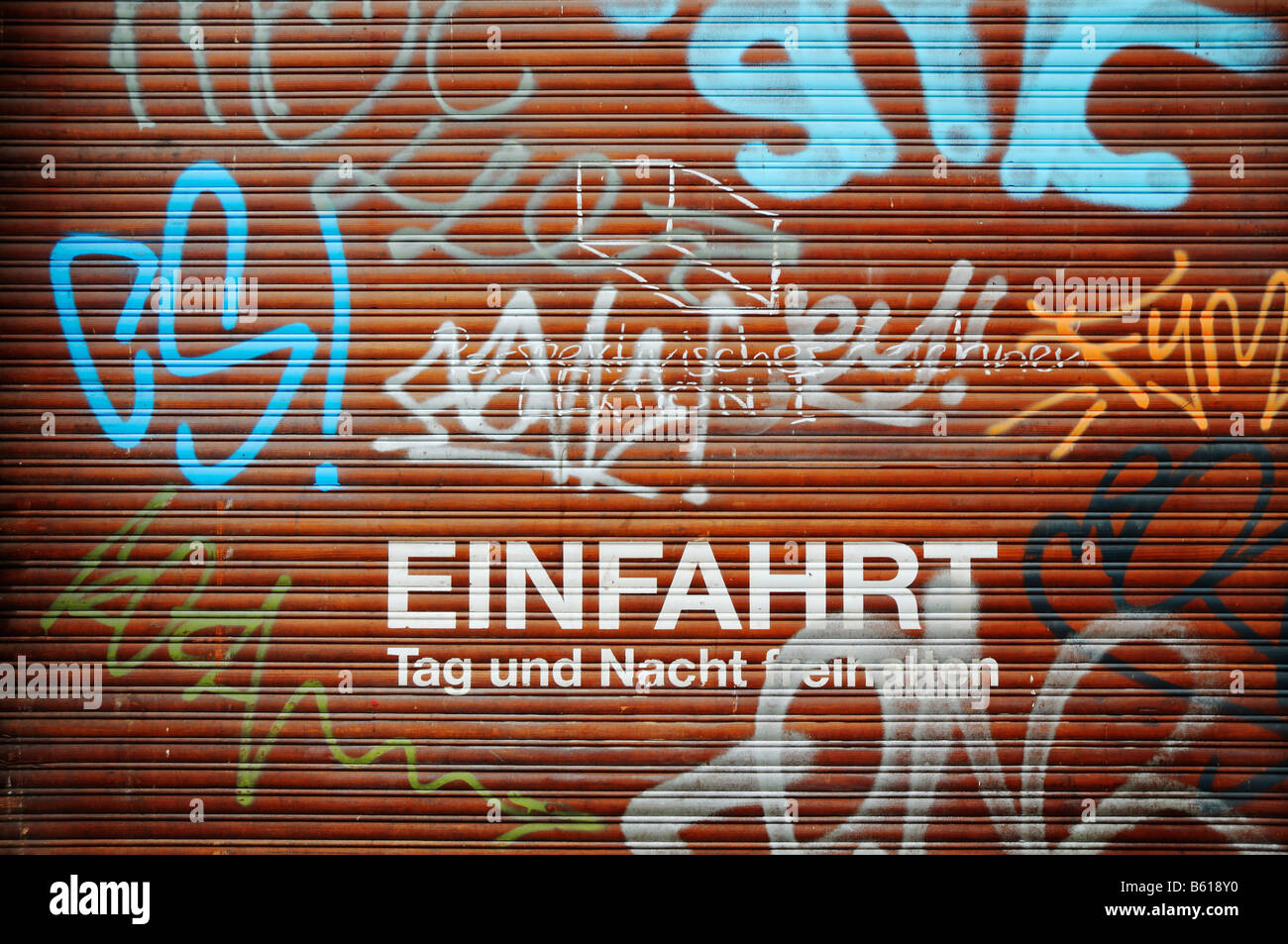 Roller shutter, keep free day and night, graffiti - Stock Image