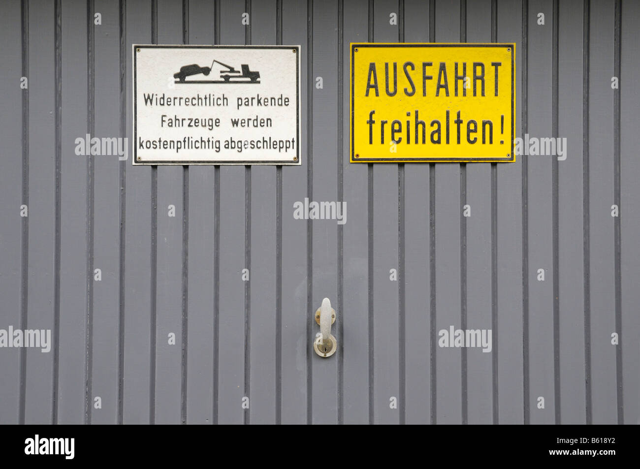 Grey garage door, sign reading unlawfully parked cars will be towed off at the owner´s expense - Stock Image