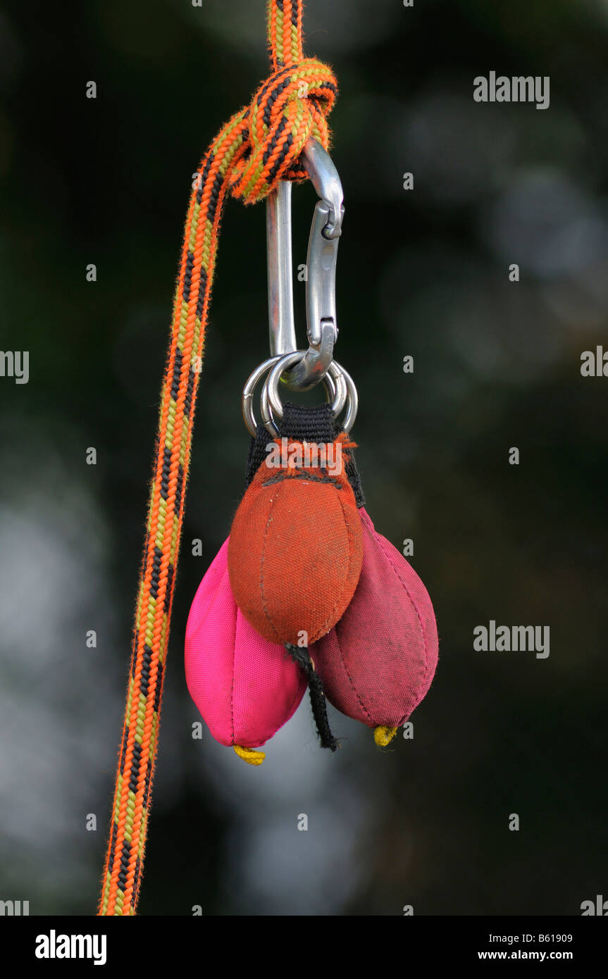 Carabiner clip with sacks of sand used as throwing weights so the rope can be positioned for rope climbing Stock Photo
