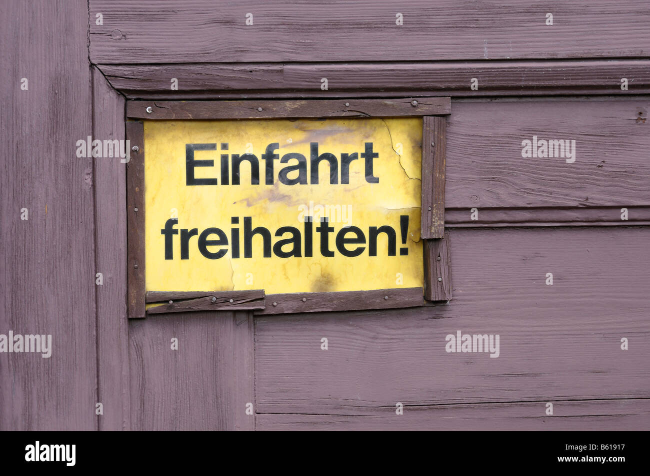 Old yellow sign on a wooden door: Einfahrt freihalten!, Keep the Entrance Clear! - Stock Image