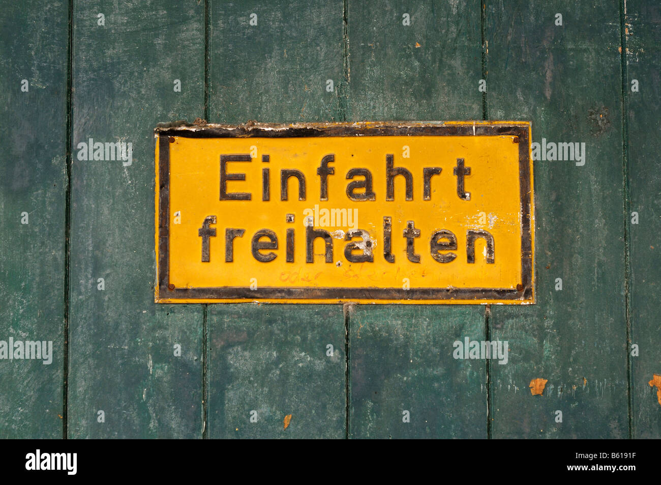Old yellow sign on a rustical wooden gate: Einfahrt freihalten, Keep the Entrance Clear - Stock Image