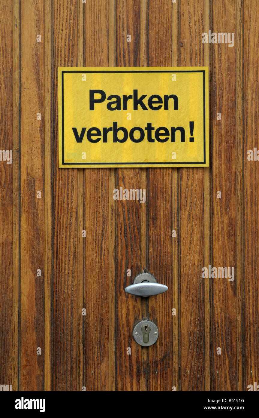 Detail of a wooden garage door with a yellow sign: Parken verboten!, No Parking! - Stock Image