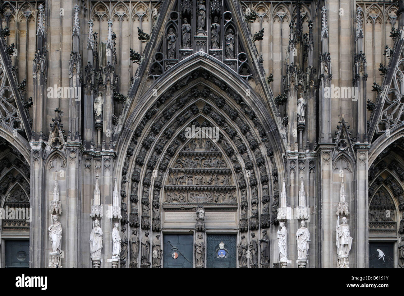 West gate of Cologne Cathedral, view of figures on the mid-gothic door, Cologne, North Rhine-Westphalia - Stock Image