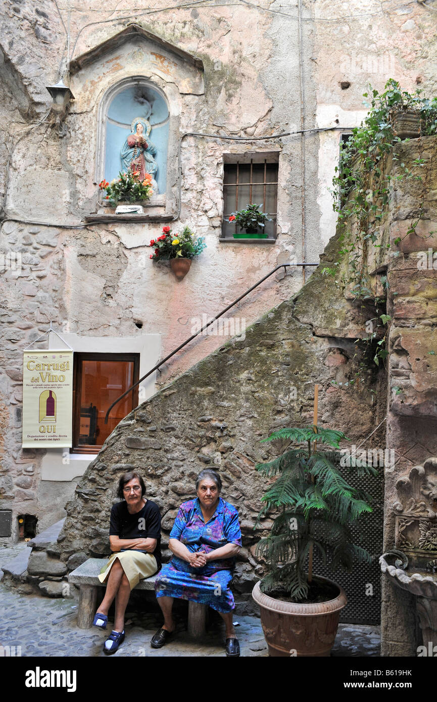 Two women sitting in an inner courtyard in Dolceacqua, Liguria, Riviera dei Fiori, Italy, Europe Stock Photo