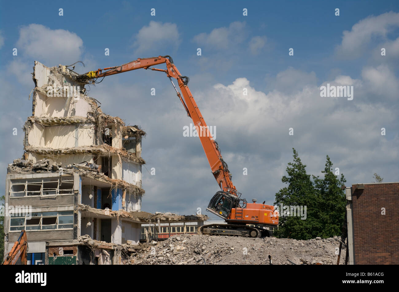 Building Being Demolished By a Daxis 470 LCH Demolition vehicle Demolishing building - Stock Image