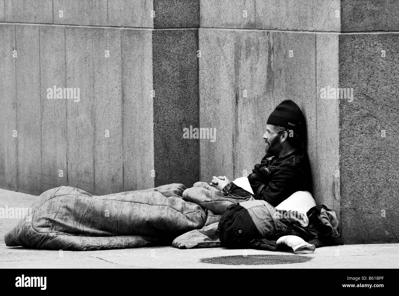 A black and white photo of a homeless man a bum a beggar sitting on the street corner of a street in a major city