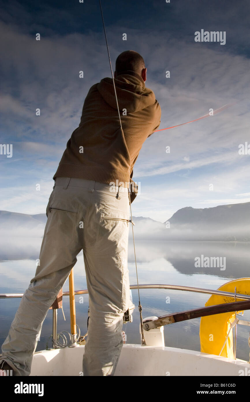 man casting off from stern of boat on derwent water , cumbria Stock Photo