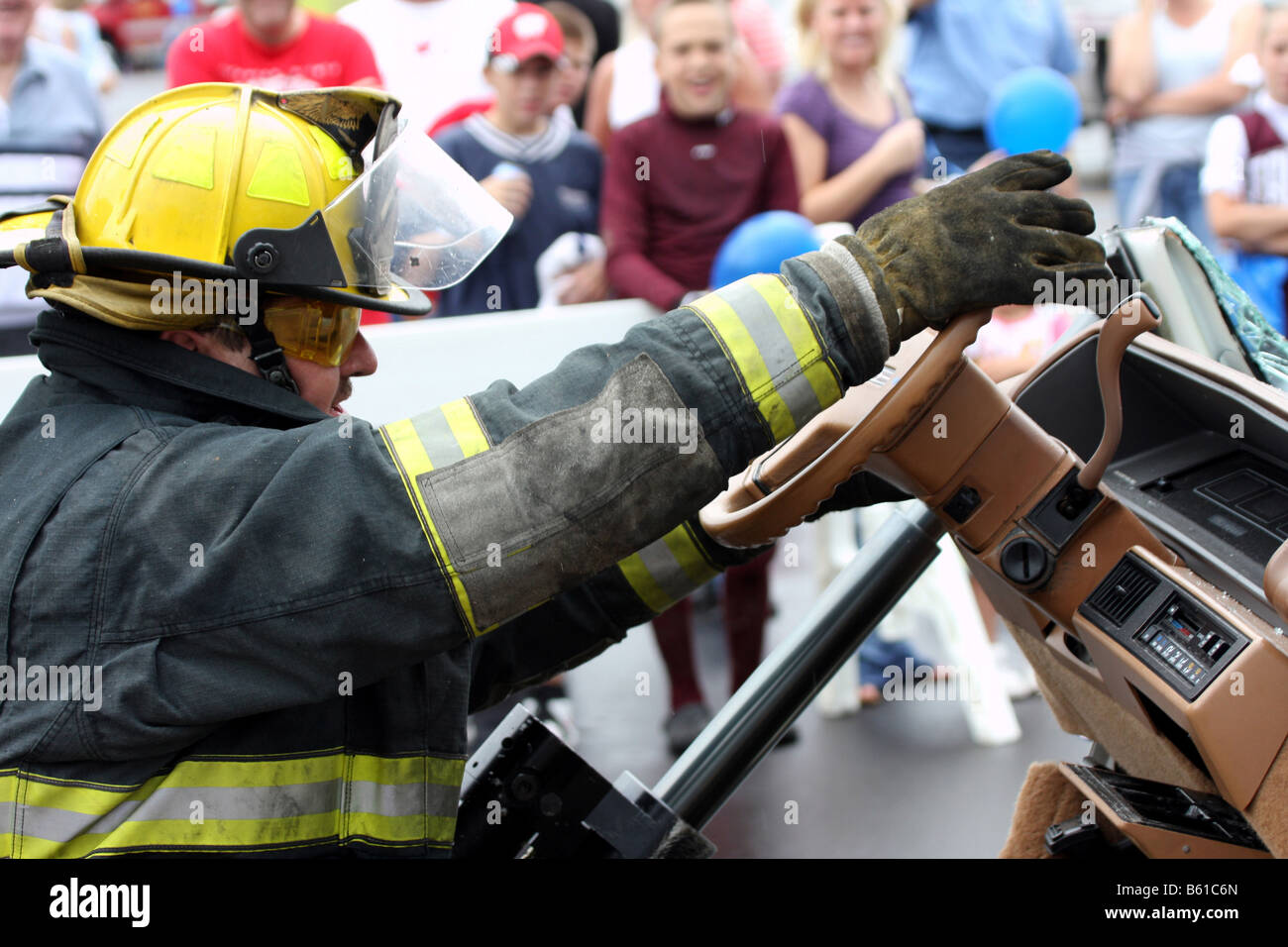 A fire fighter at a Fire Safety Fair having fun by sitting in the drivers seat after the car has been taken apart - Stock Image