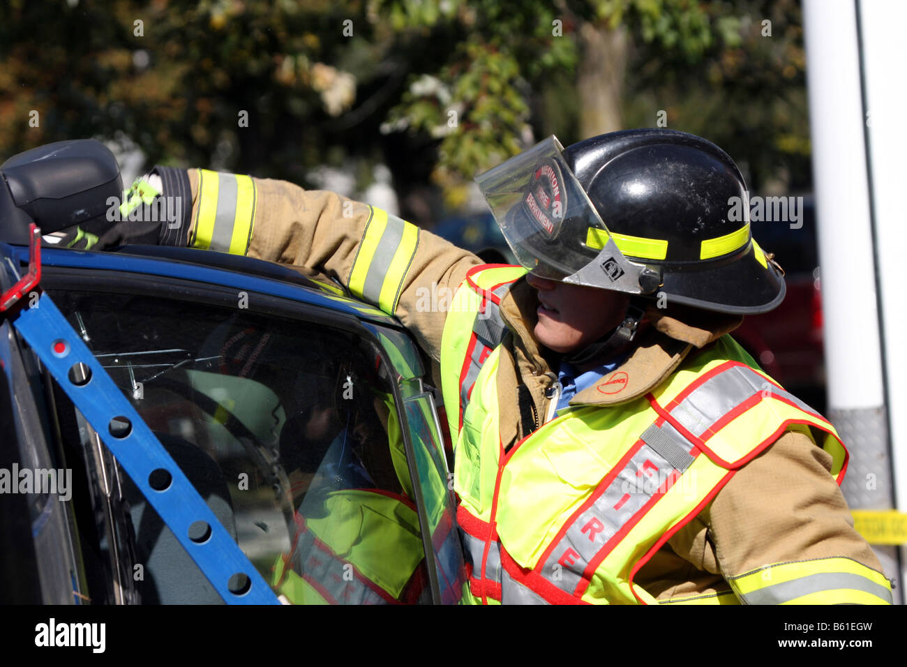 The windows are broken and the firefighter is removing glass remnants from the door frame of a stabilized rollovered - Stock Image
