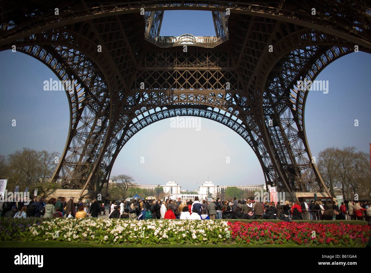 Visitors to the Eiffel Tower observe Paris' iconic structure - Stock Image