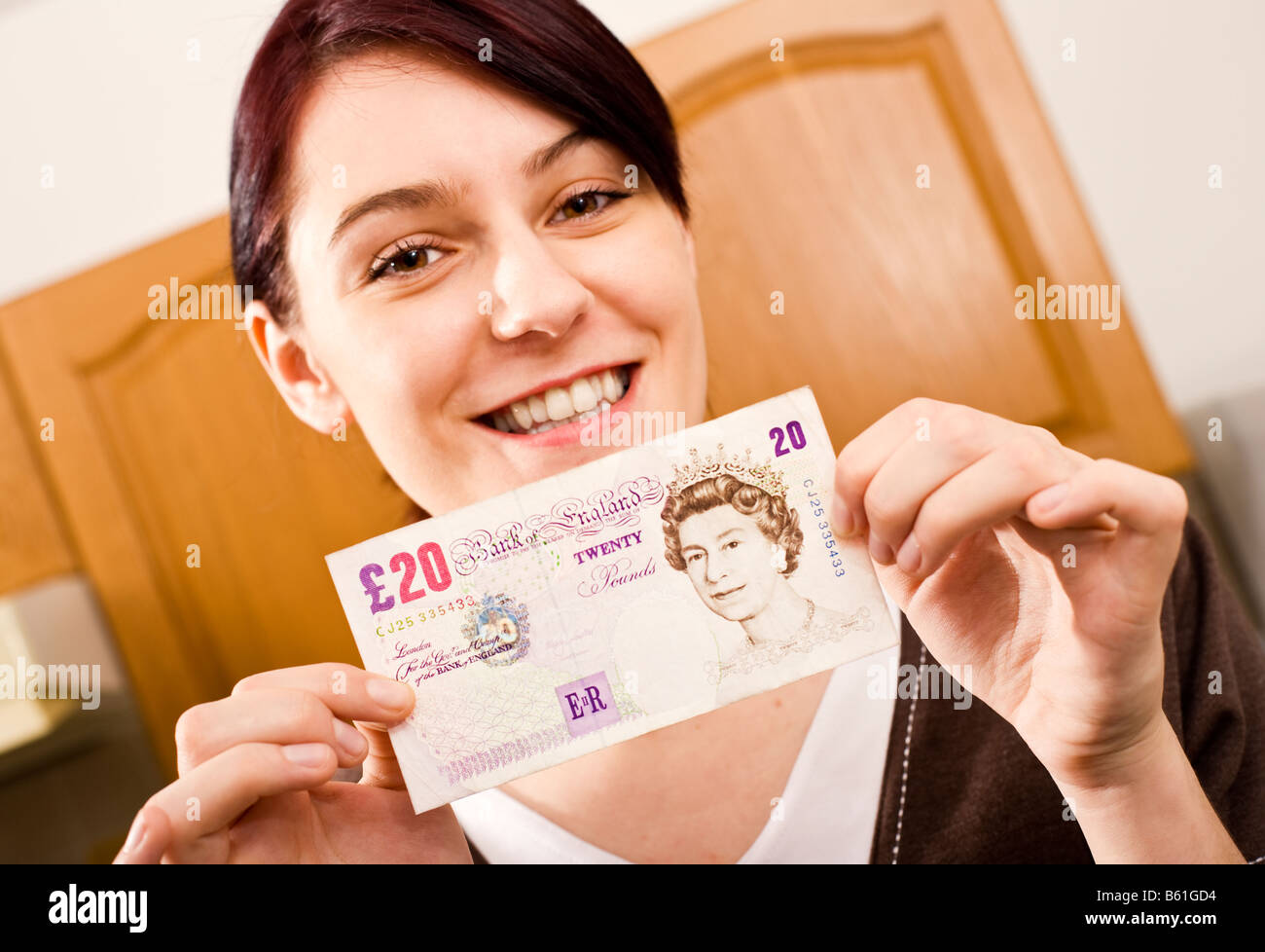 Young woman at home holding a 20 note and smiling looking at camera - Stock Image
