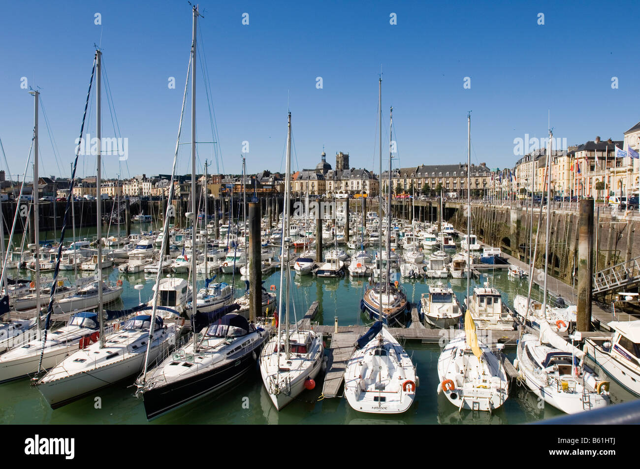 The tidal dependent part of the harbour, surrounded by houses of the historic town centre, yachts in the harbour, - Stock Image