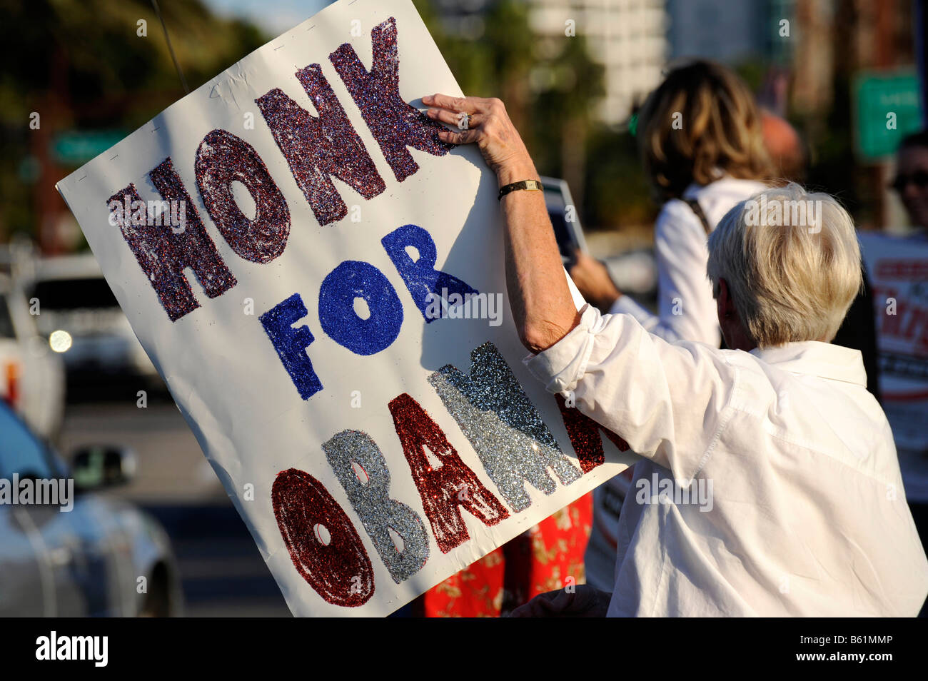 Female senior citizen shows sign for Barack Obama for President on busy road - Stock Image