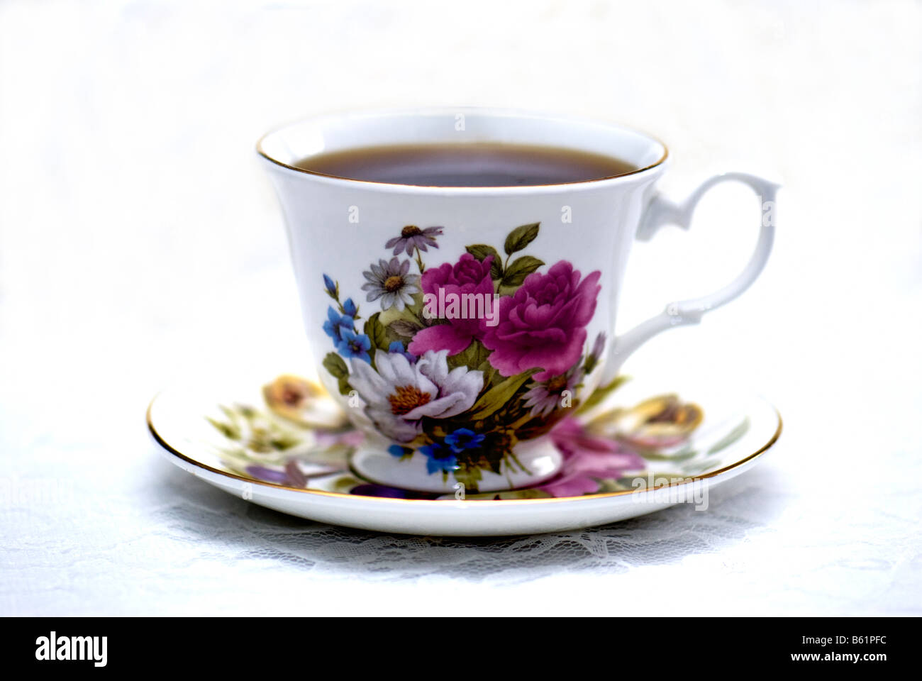 A cup of coffee in a floral cup and saucer, resting on a lace tablecloth. Stock Photo