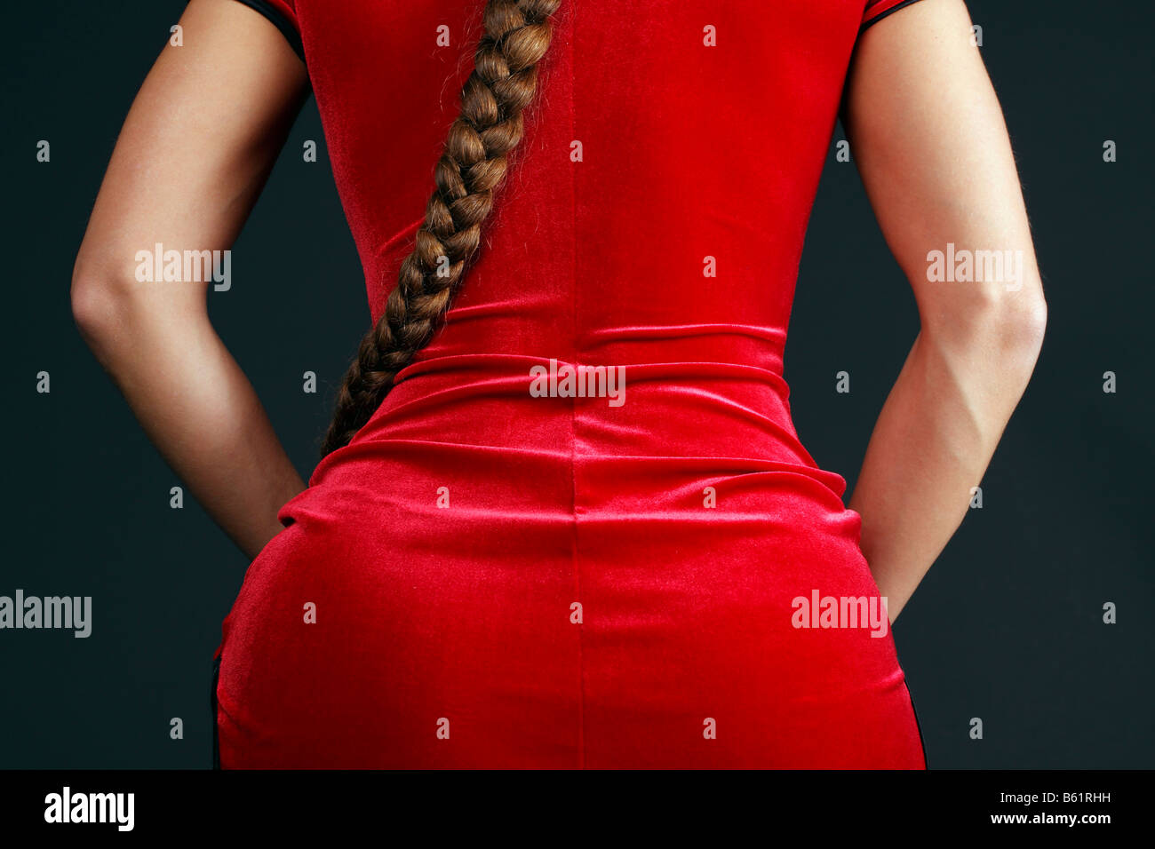 Woman wearing a red velvet dress and pony tail from behind, partial view - Stock Image