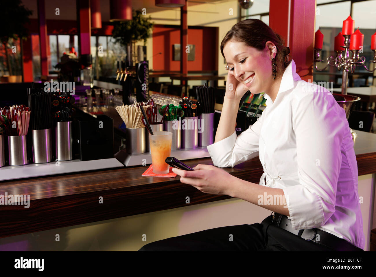 Young woman with a mobile telephone in a bar - Stock Image