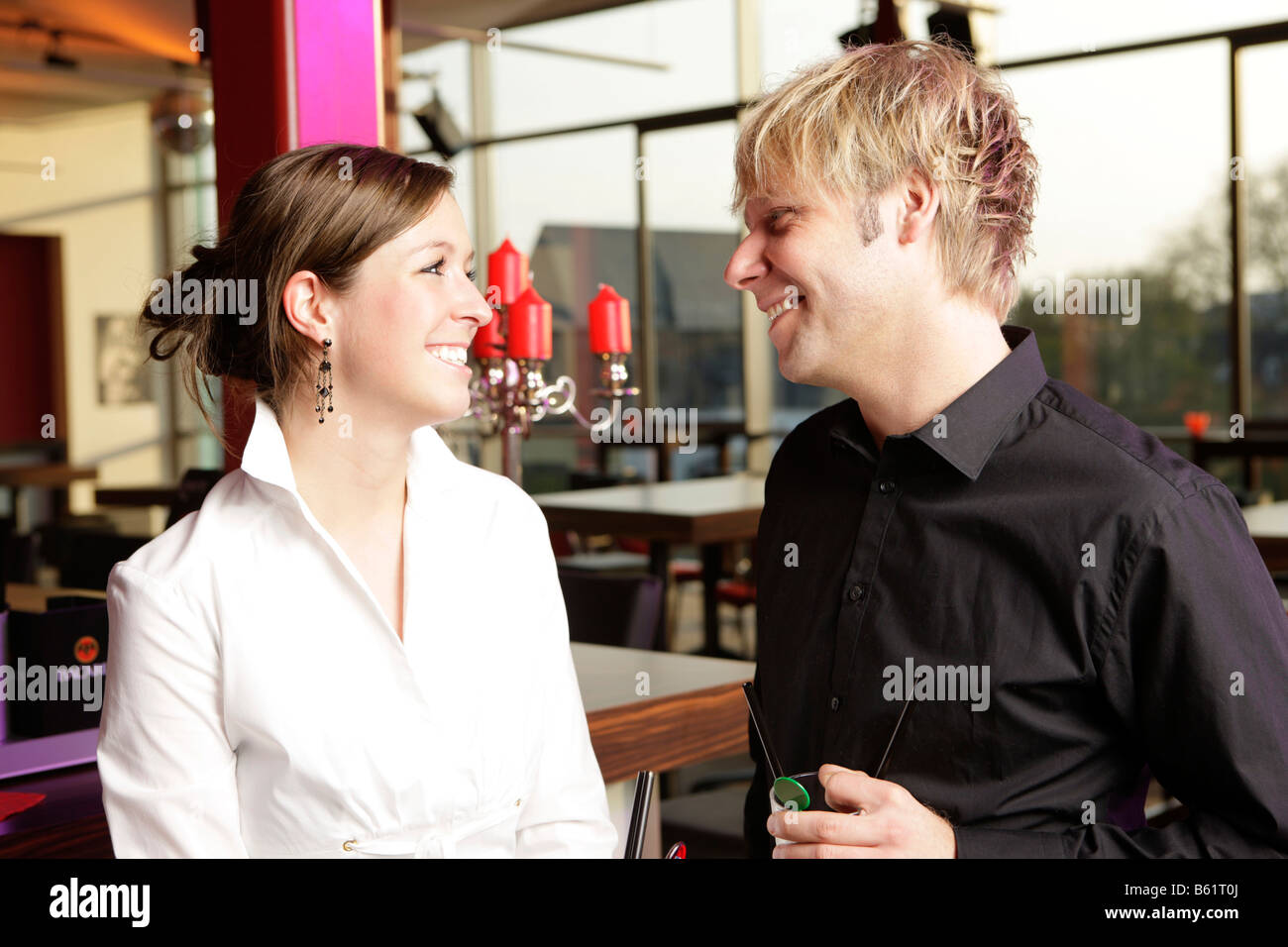 Man and woman smiling in a bar - Stock Image