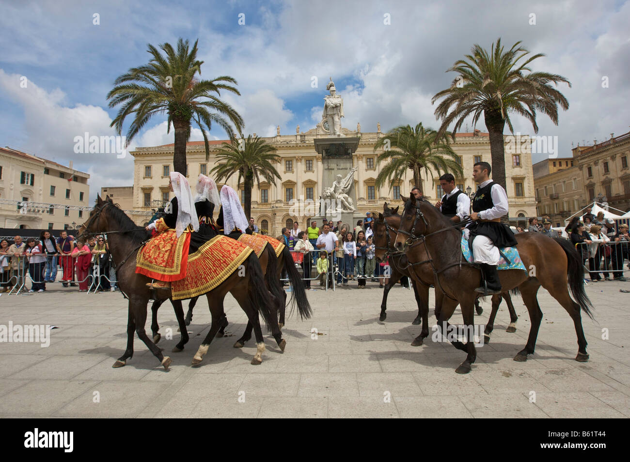 Men and women riding horses while wearing traditional costumes at the Cavalcata Sarda parade on the Piazza Italia - Stock Image