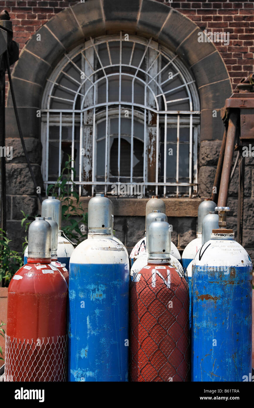 Compressed gas bottles with oxygen and acetylene for gas welding in front of an old building, building site, Rhine - Stock Image