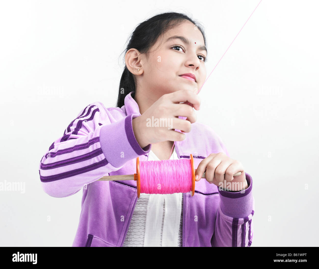 a smart asian girl of indian origin flying a kite - Stock Image