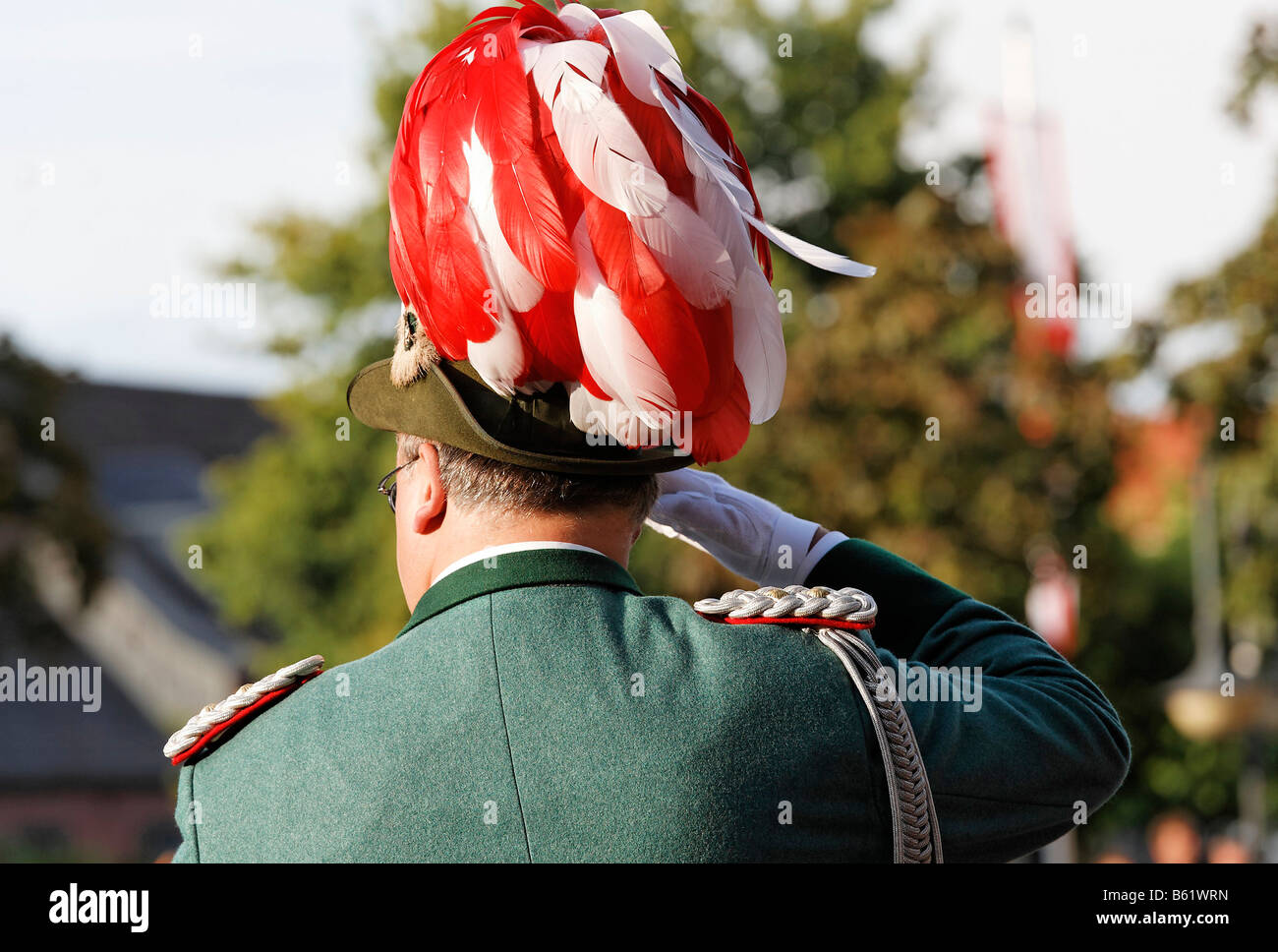 Gunman in uniform with a red and white feather hat, saluting, back-view, Schuetzenumzug in Xanten, Lower Rhine region, - Stock Image
