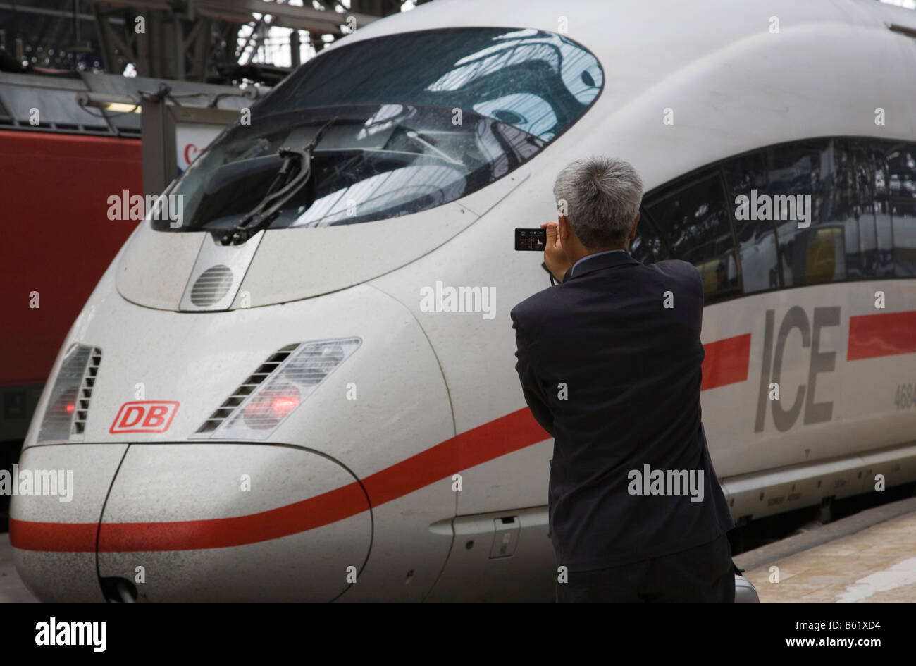 Asian tourist taking a photo of the front of an ICE in Frankfurt main station, Frankfurt am Main, Hesse, Germany, Stock Photo