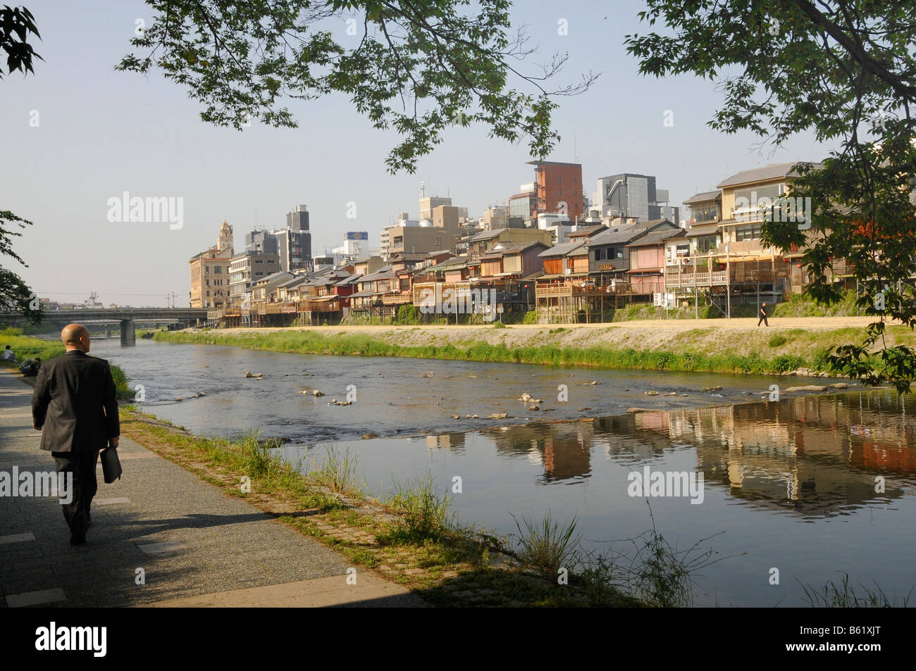 Traditional Japanese houses alongside the Kamo River in front of the high-rise apartment buildings of the city centre, - Stock Image
