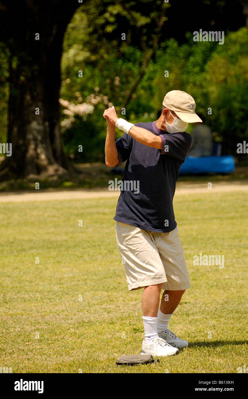 Golfer training without a club in the botanical gardens, Kyoto, Japan, Asia - Stock Image